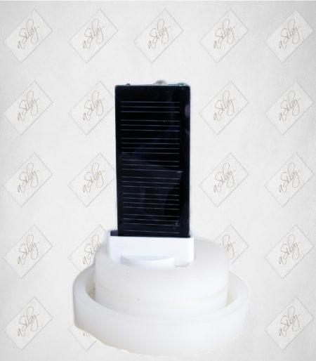 Candela perenne ad energia solare composta da pannello solare con luce e candela in vetro con base.